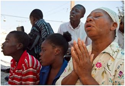 Woman praying surrounded by other Haitians